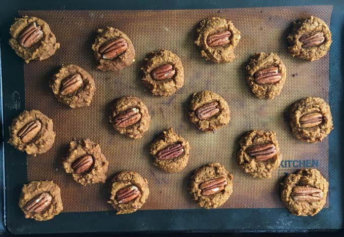 pecan pumpkin breakfast cookies on a silicone mat on a cookie tray