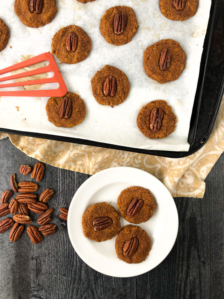 aerial view of a cookie sheet and white plate with healthy pecan pumpkin cookies and scattered pecans