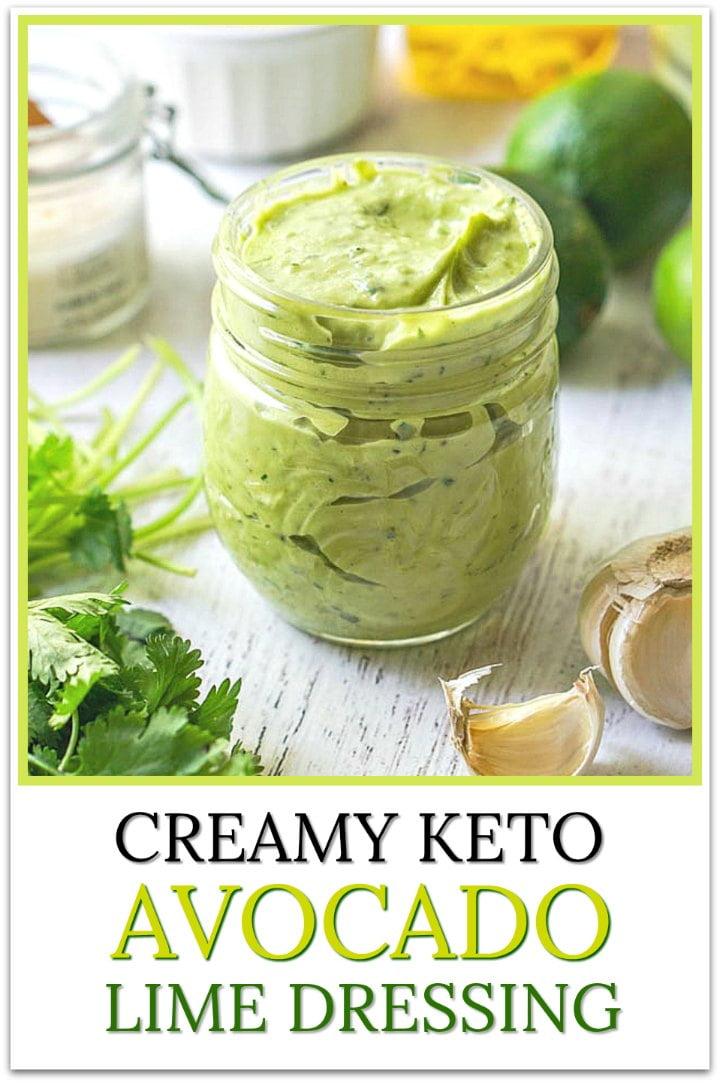 jar of creamy keto avocado lime dressing with garlic cloves, cilantro and text