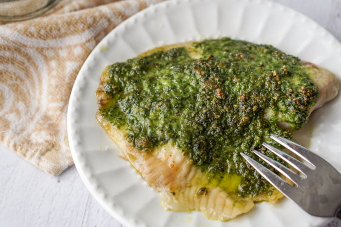 This low carb pesto tilapia dinner can be made in less than 20 minutes. The pesto is made from fresh spinach and toasted walnuts and adds lots of healthy color and flavor to this mild white fish.