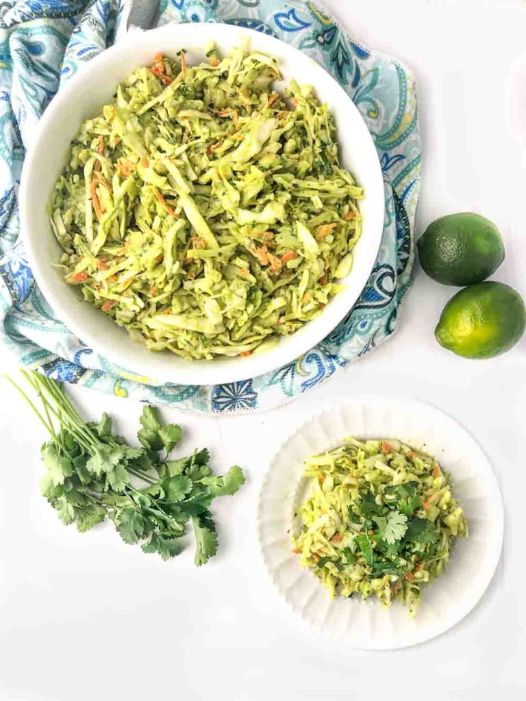 aerial view of a white bowl and plate with dairy free coleslaw, fresh limes and cilantro