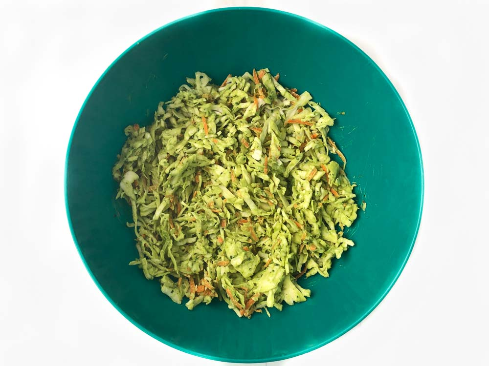 big green bowl with cabbage and avocado dressing mixed