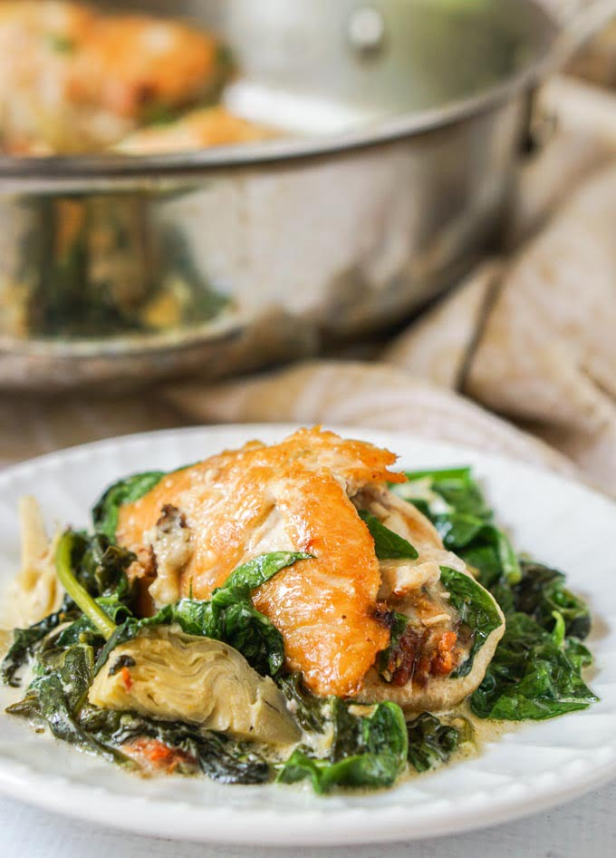 This tapenade stuffed chicken with creamy spinach & artichokes dish is a deliciously low carb dinner you make in one pan. The creamy spinach and artichokes go perfectly with the tasty tapenade that the chicken is stuffed with and each serving is just 4.7g net carbs.