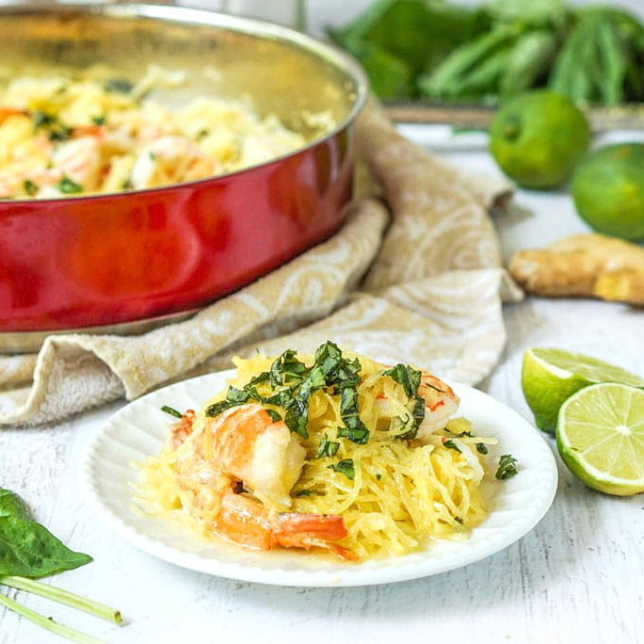 white dish with a serving of coconut basil shrimp spaghetti squash with a red pan in background, fresh limes and basil