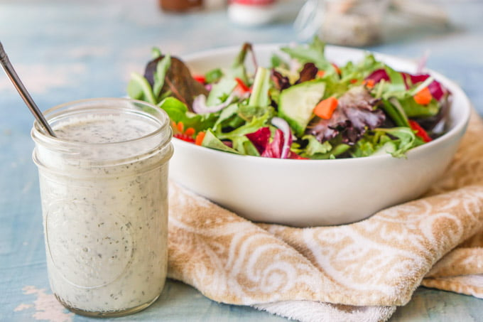 jar of homemade ranch and white bowl of salad on a beige tea towel