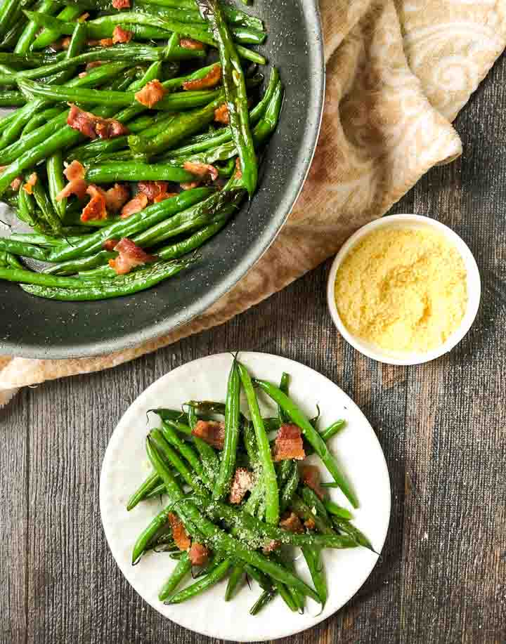 pan and white plate with green beans side dish and a bowl of parmesan cheese