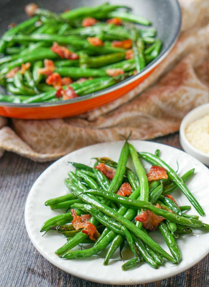 white plate with low carb green beans & bacon with skillet in the. background
