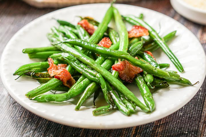 closeup of white plate with a serving of keto green beans and bacon