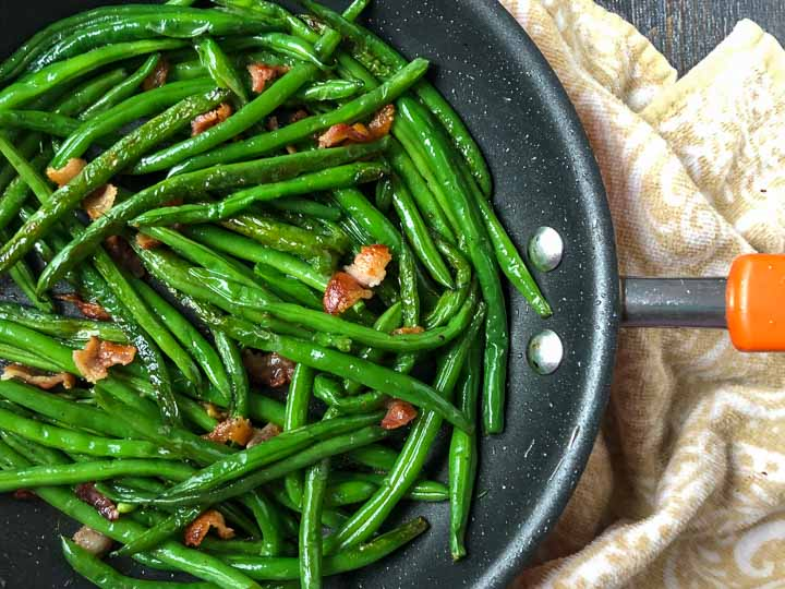 skillet with green beans and bacon on beige tea towel
