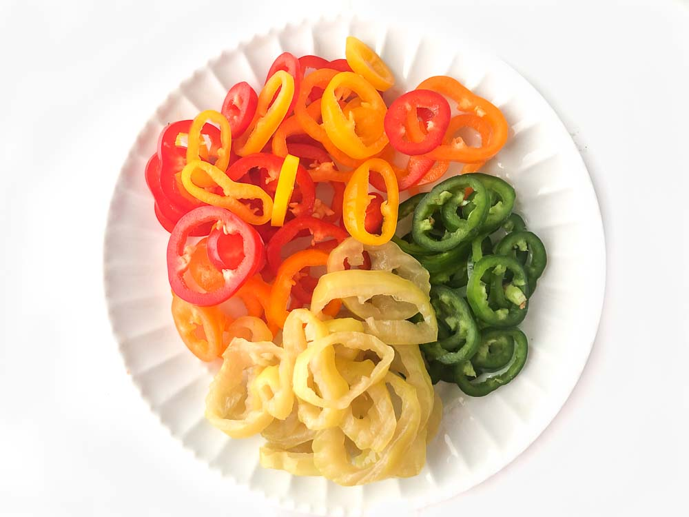 white plate with 3 kinds of peppers - sweet bell, jalapeno and banana pepper rings