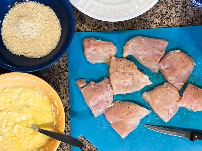 raw chicken on cutting board with almond flour and egg mixture