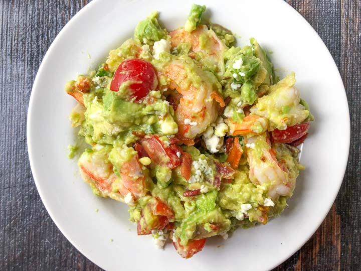 white plate with a serving of shrimp salad with avocados and bacon