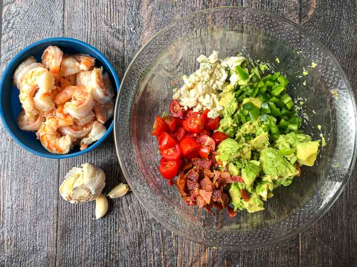ingredients for keto avocado shrimp salad: cooked shrimp, garlic, tomatoes, blue cheese, avocados, bacon, jalapenos