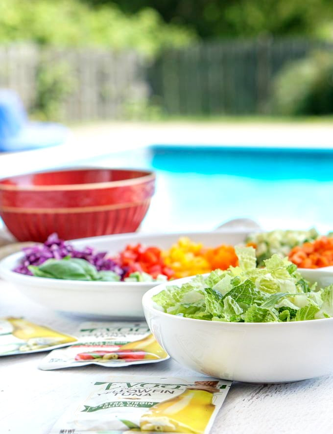 bowl of lettuce and platter of fresh rainbow colored chopped vegetables with a red bowl and pool in the background