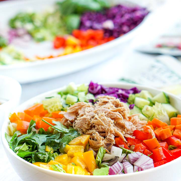 white bowl with chopped veggies and tuna to make a spring roll salad with a platter in background