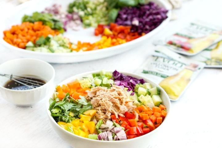 white bowl with chopped veggies and tuna on top with a bowl of dressing with a whisk and packets of tuna in the background