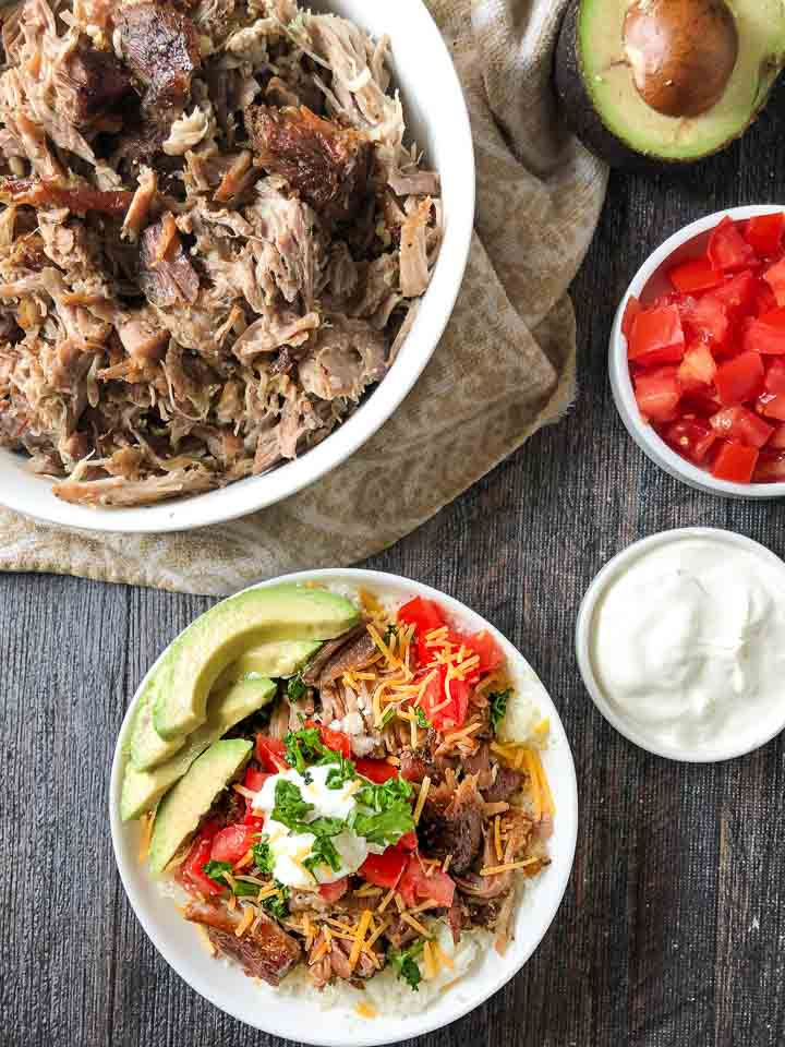 white bowl with low carb pulled pork and a cauliflower rice bowl with toppings and bowls of sour cream and chopped tomatoes