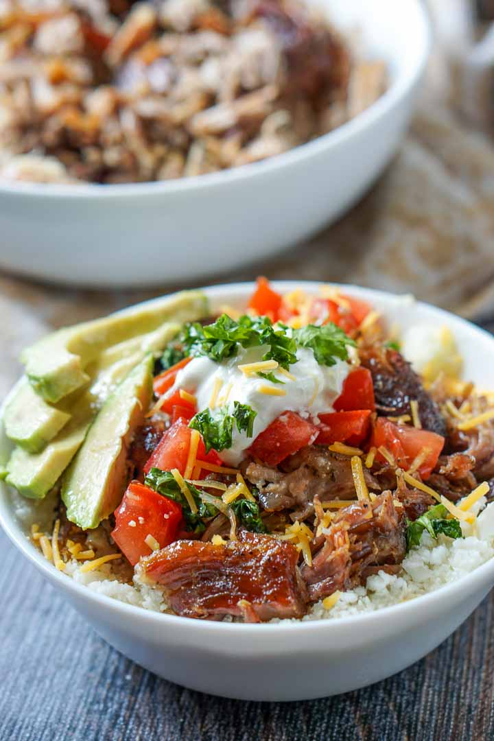 closeup of a cauliflower rice bowl topped with pulled pork, tomatoes, cheese, avocados and sour cream with white bowl of pulled pork in background