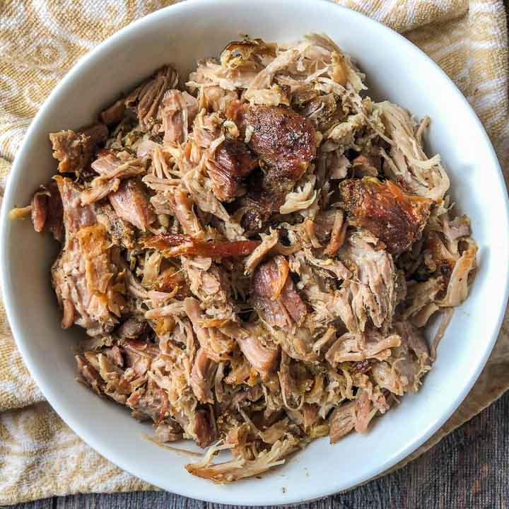 white bowl with slow cooker garlic pulled pork with beige paisley tea towel underneath