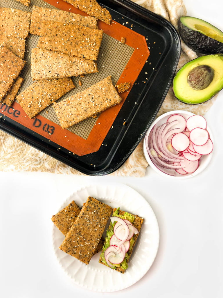 baking tray and white plate with homemade crispbread keto crackers and an avocado cut in half and radish slices