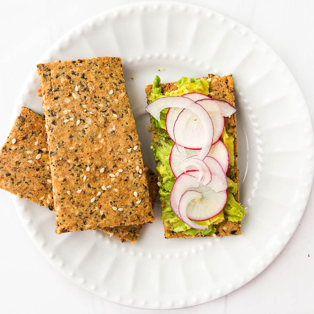 white plate with homemade Norwegian crispbread with avocado and radish