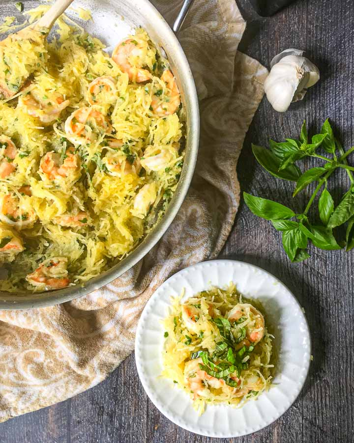 aerial view of a plate of shrimp scampi spaghetti squash and a pan full with fresh basil sprig