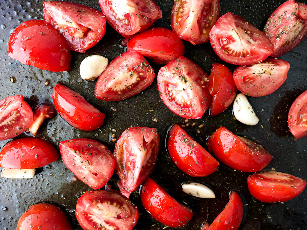 baking tray with raw fresh tomatoes and garlic cloves