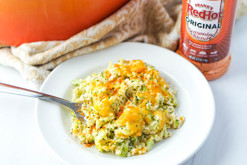 white dish with cheesy cauliflower and a bottle of RedHot seasoning