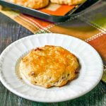 cheddar scone on white plate and cookie sheet in background - text overlay