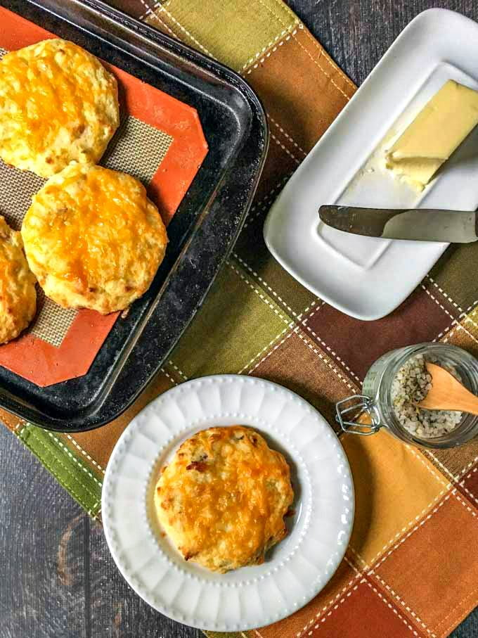 bacon cheddar scone on white plate and butter dish with autumn placemat