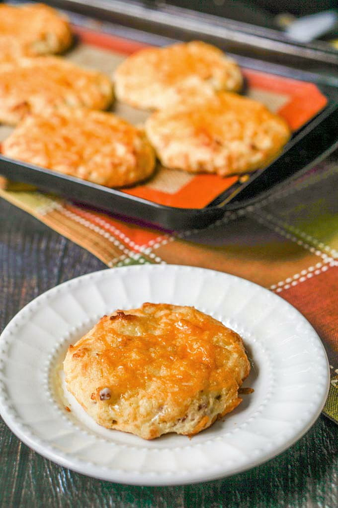bacon cheddar scone on white plate with cookie sheet in background