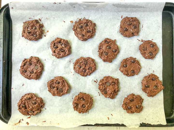 cookie sheet with parchment paper and raw brownie cookies ready to bake