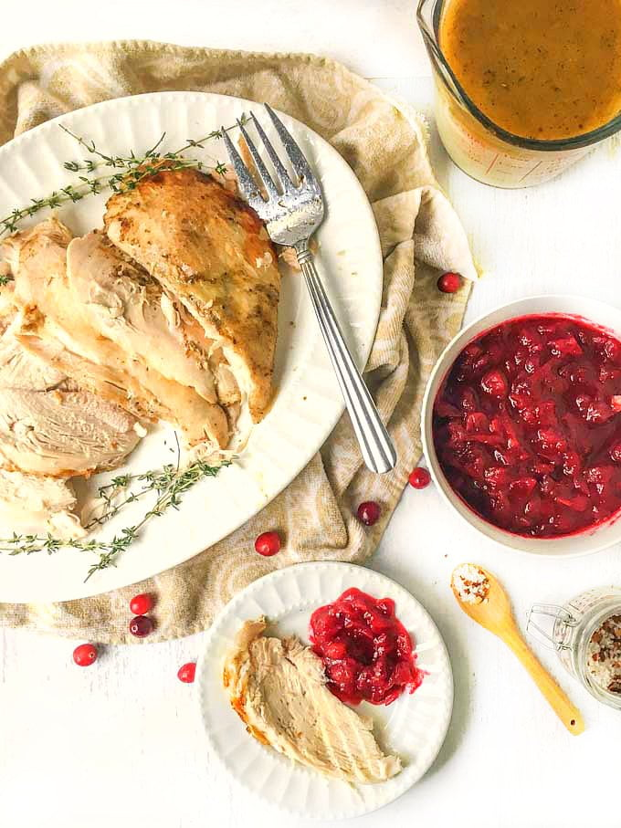 white plate and platter with sliced turkey and a bowl of gravy and a bowl of cranberry sauce