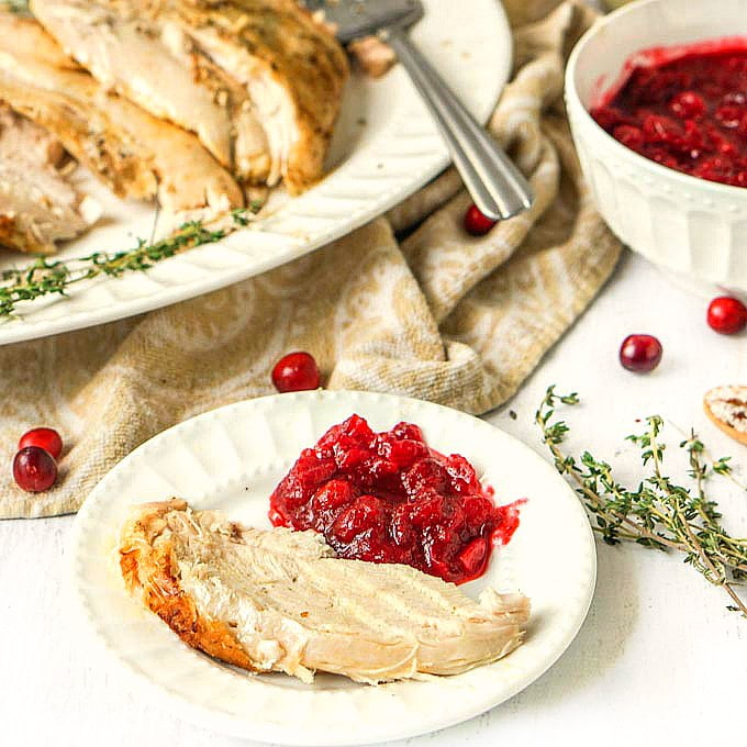 white plate with a slice of instant pot cookies turkey breast with cranberry sauce  on the side