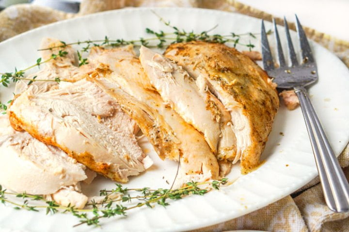 white platter with sliced turkey breast and a large fork and thyme sprigs