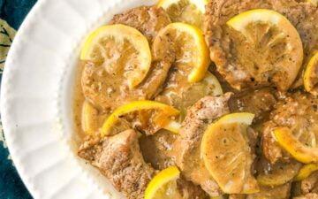 white platter with lemon butter pork tenderloin slices and green tea towel underneath