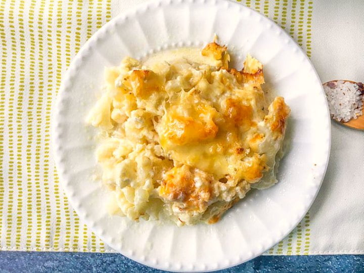 white plate with a serving of cheesy cauliflower casserole