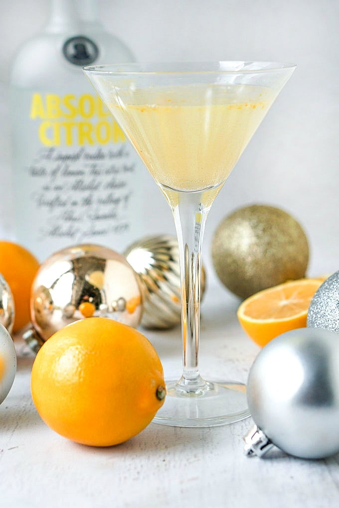 keto lemon drop martini with cut Meyer lemon and ornaments and bottle in background