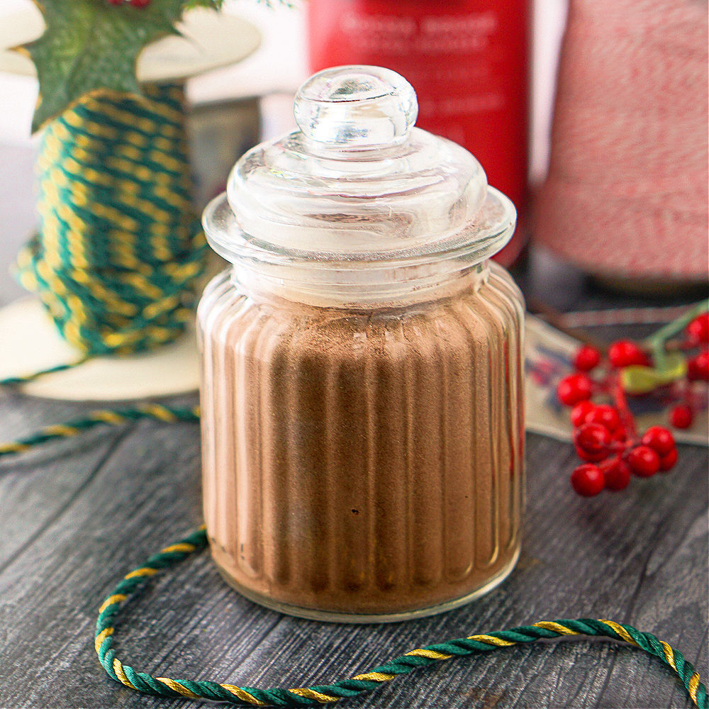 glass decorative jar with keto hot chocolate mix and Christmas decoration sin the background