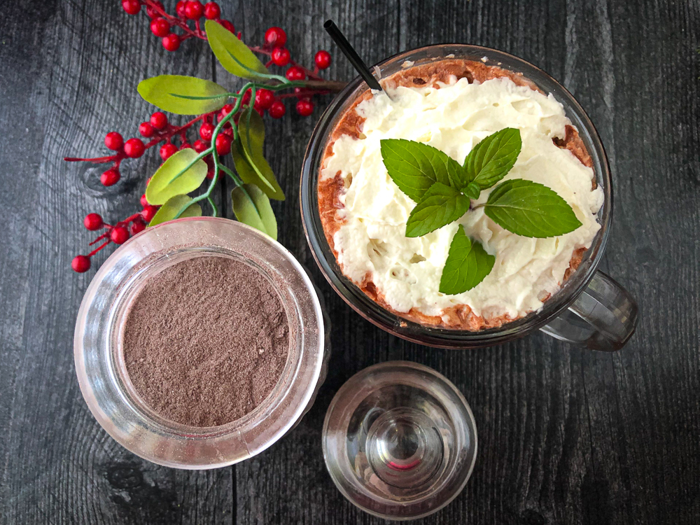 jar of hot chocolate mix and a glass of  of cocoa topped with whipped cream