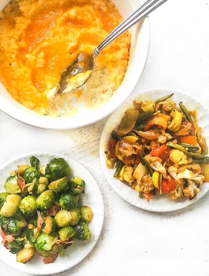 aerial view of low carb side dishes: twice baked cauliflower mash, roasted vegetables, bacon and Brussel sprouts