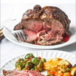 white plate with roast beef and vegetables with rib roast in the background and text