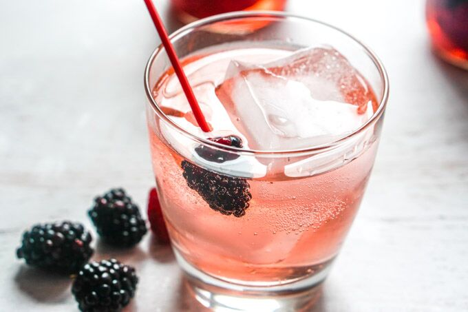 A light pink drink with a blackberry on the straw.