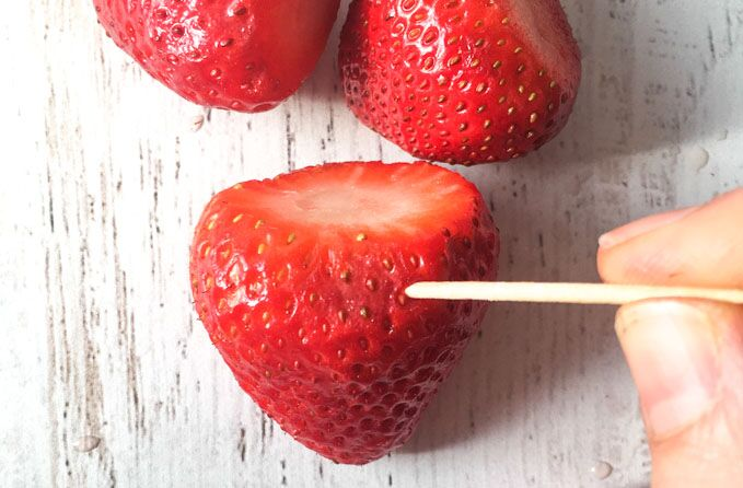 A toothpick piercing a strawberry.