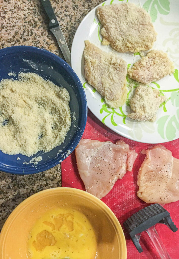 dish and bowls with breaded chicken cutlets ready to fry