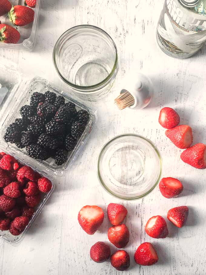 Aerial photo of berries and empty jars.