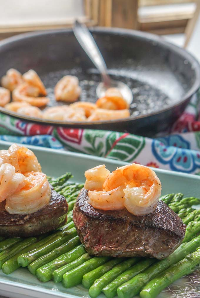 Long photo of steaks with a pan of shrimp in background.