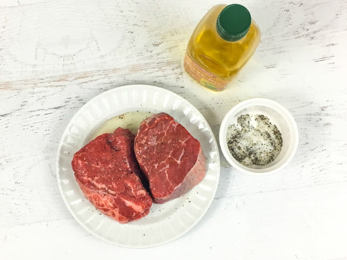 Aerial view of raw steaks with olive oil and sat and pepper.