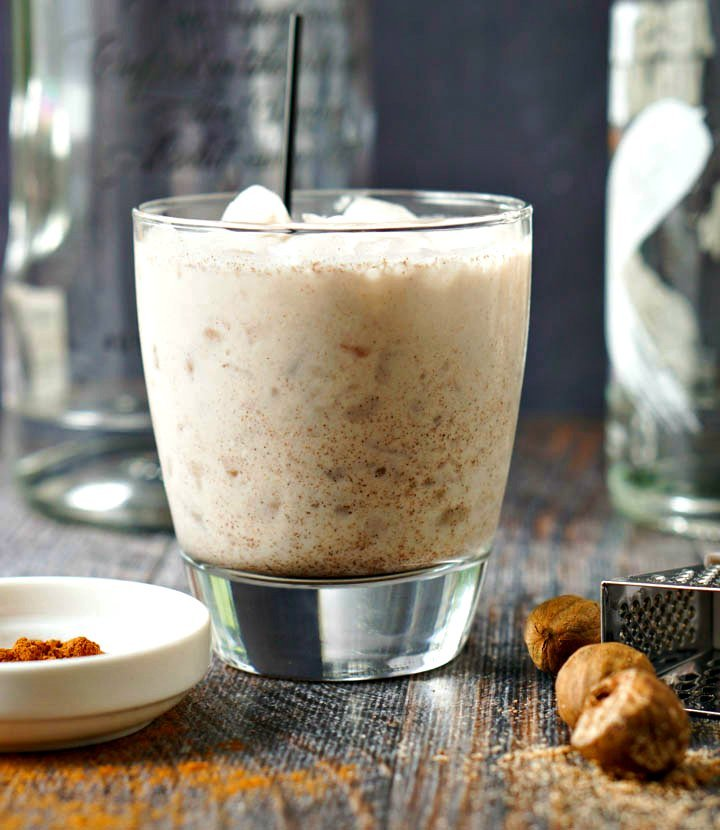 closeup of glass with low carb rum chata drink and a bowl of cinnamon and fresh nutmeg