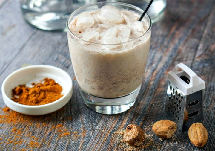 glass with low carb rum chata drink and a bowl of cinnamon and fresh nutmeg